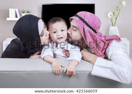 Two young Arabian parents kissing their son while sitting on the sofa in the living room - stock photo
