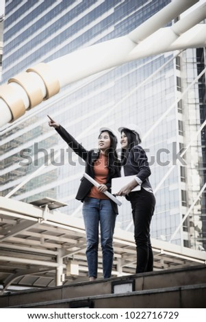Two Young architects looking at blueprint in front of construction site building.