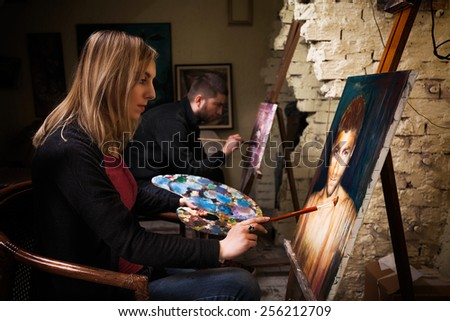 Two young artists working on oil paintings in art studio. - stock photo