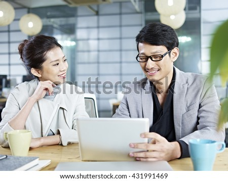 two young asian corporate people discussing business in office using tablet computer. - stock photo