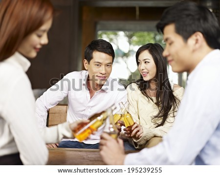 two young asian couples drinking beer together. - stock photo