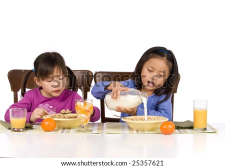 Two young Asian Girls eating a healthy Breakfast