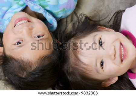 Two young asian girls having fun. Family, sisters, siblings - stock photo