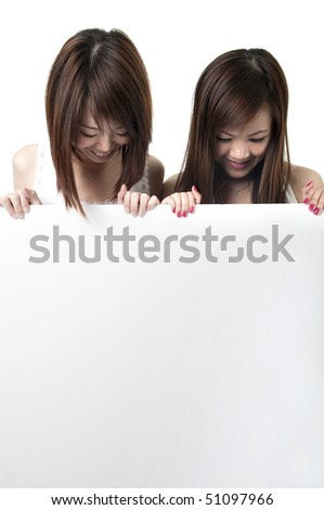 two young asian girls holding a blank cardboard - stock photo
