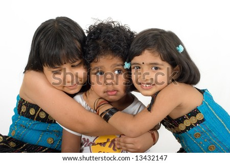 Two young Asian girls in a traditional costume hugging a boy