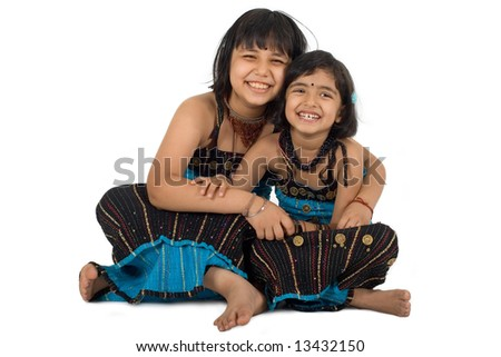 Two young Asian girls in traditional costume showing sisterly affection and smiles - stock photo