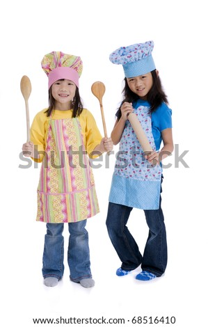Two young asian girls preparing to cook something - stock photo