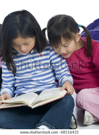 Two young asian girls reading a book - stock photo