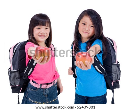 Two young Asian Girls with apples for the teacher - stock photo
