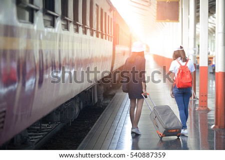 Two Young Asian tourist with luggage waiting train in station