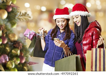 two young asian women looking at mobile phone during christmas shopping