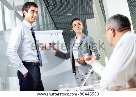 Two young associates by whiteboard looking at senior chief at meeting - stock photo