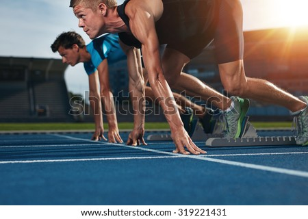 Two young athletes at starting position ready to start a race. Sprinters ready for race on racetrack with sun flare. - stock photo