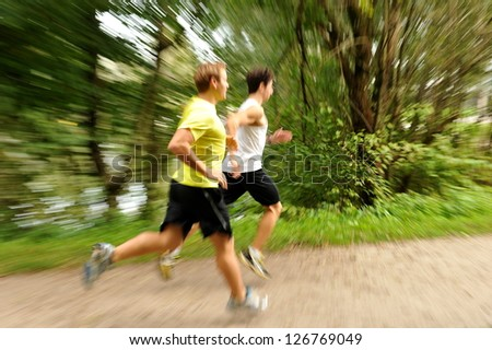 Two young athletes jogging / running in the park, Motion blurred - stock photo