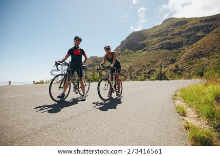 Two young athletes taking a break from cycling on country road. Cyclist training for triathlon competition on open road with bicycles. - stock photo