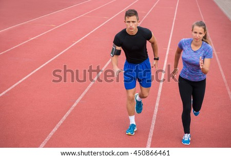 Two young athletic people running on race track. Male and female professional athletes running on athletics race track.