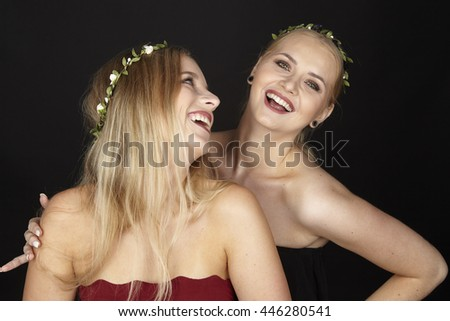Two young attractive blonde girlfriends laugh and wear a floral wreath in her hair. She touches her pal with her hand at the shoulder.