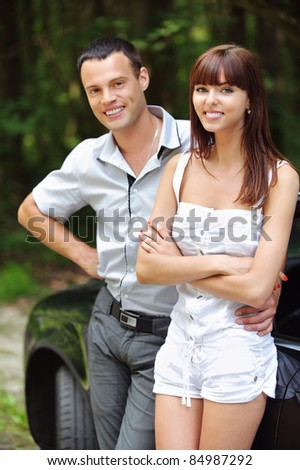 Two young attractive people: beautiful brunette woman and handsome man standing near car at summer green park. - stock photo