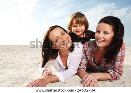 Two young attractive woman and small child on the beach.