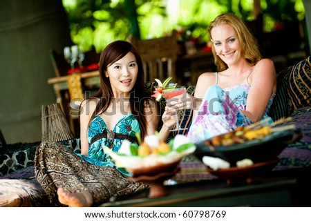 Two young attractive women having lunch and drinks at a restaurant - stock photo