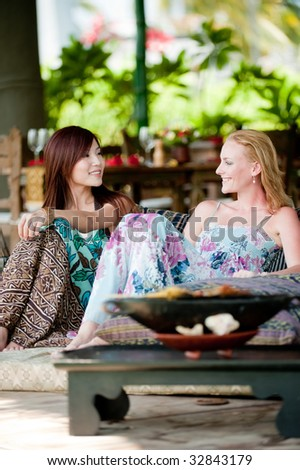 Two young attractive women having lunch and drinks on vacation - stock photo