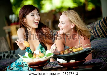 Two young attractive women having lunch on vacation - stock photo