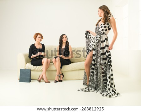 two young attractive women sitting on sofa and looking at another modeling a dress - stock photo