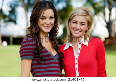 Two young attractive women standing together at college