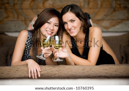 Two young attractive women with wine lying on bed