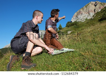 Two young backpackers reading a map and pointing on a mountain summit - stock photo