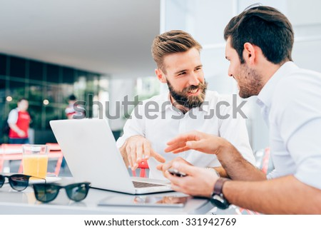 Two young bearded caucasian modern business man sitting in a bar, using laptop, looking each other, smiling and chatting - business, work, technology concept  - stock photo