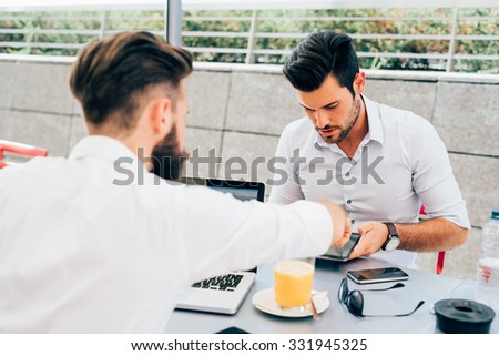Two young bearded caucasian modern business man sitting in a bar, using tablet and laptop, looking downward, touching the screen - business, work, technology concept - focus on black hair man - stock photo