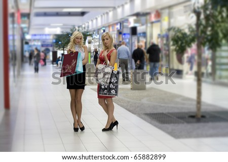 two young beautiful and elegant woman inside a commercial center go for shopping with shoppingbags - stock photo