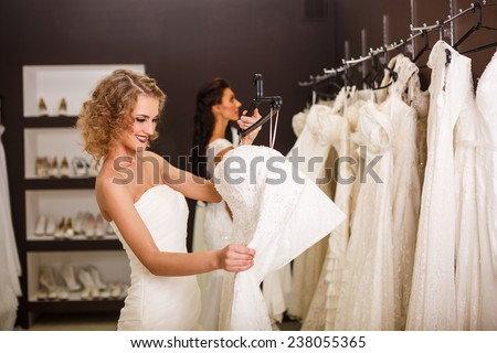 Two young beautiful brides trying her dress in shop - stock photo