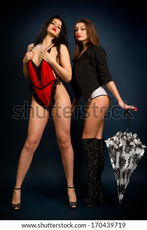 Two young beautiful brunette on a dark background - stock photo