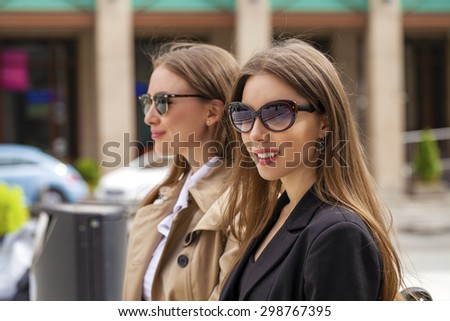 Two young beautiful business women in sunglasses in the summer city - stock photo