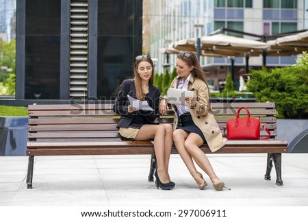 Two young beautiful business women sitting on a bench in the summer city - stock photo