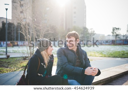Two young beautiful caucasian woman and man lovers sitting outdoor in the city back light looking one in the other eyes smiling - love, relationship concept - stock photo