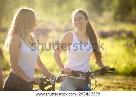 Two young beautiful cheerful women girlfriends wearing jeans shorts on bicycles in park on sunny summer day, having good time, happy laughing together - stock photo