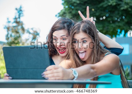two young, beautiful female friends taking a crazy selfie for social networks