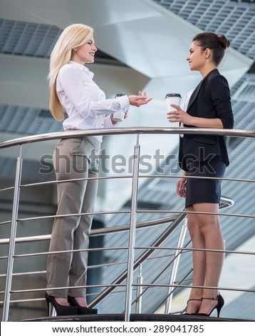 Two young beautiful female office workers talking during coffee-break. Full length. - stock photo