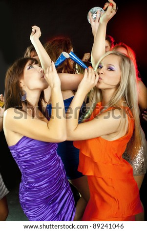 Two young beautiful friends  dancing at a disco. New Year - stock photo
