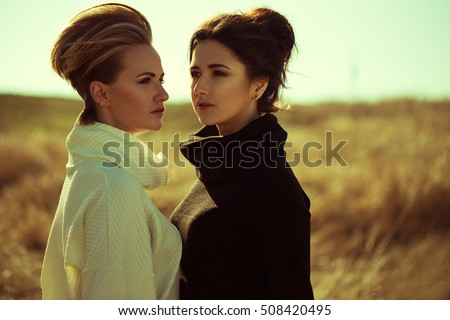 Two young beautiful girl in the field. Fashion portraits of blond and brunette girls, european and italian appearance, in a different colors of pullover. perfect make up, hairdo and stylish look