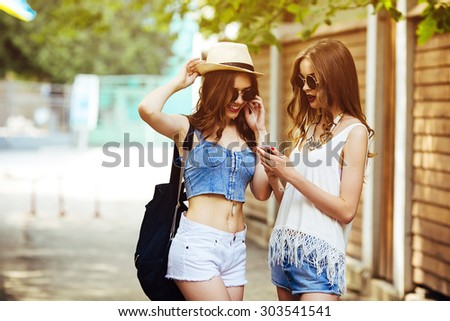 Two young beautiful girls are walking through the city and listen to music