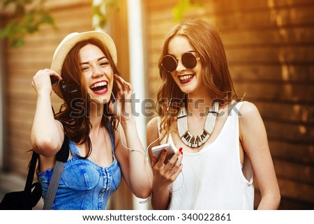 Two young beautiful girls are walking through the city and listen to music - stock photo