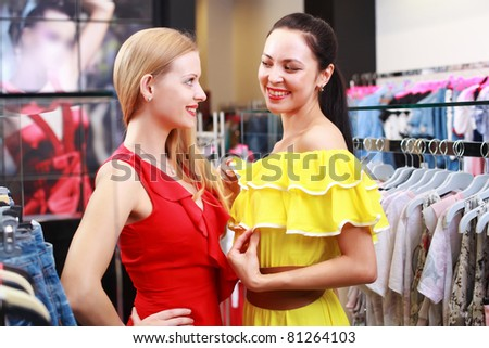 Two young beautiful girls choose their clothes in the store