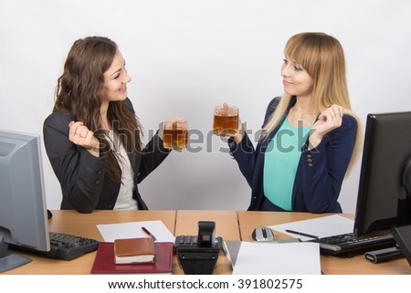 Two young beautiful girls drink tea, office behind a desk in transparent glasses and animated conversation - stock photo
