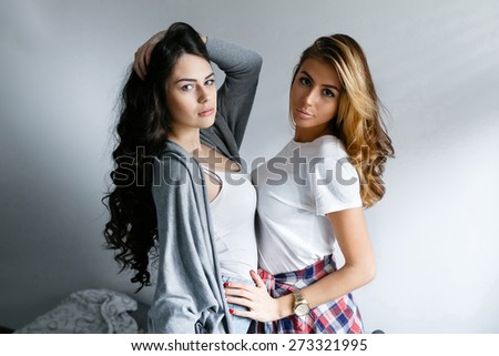 Two young beautiful girls laughing and posing on wall background. Fresh style, life style.
