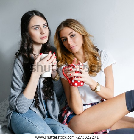 Two young beautiful girls laughing and posing with cups and inhale the aroma of drinks in the bedroom sitting on the bed in the morning.Fresh style, life style. - stock photo