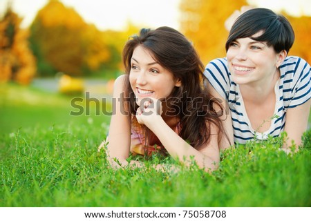 Two young beautiful girls lying on the lawn on a background of green nature - stock photo